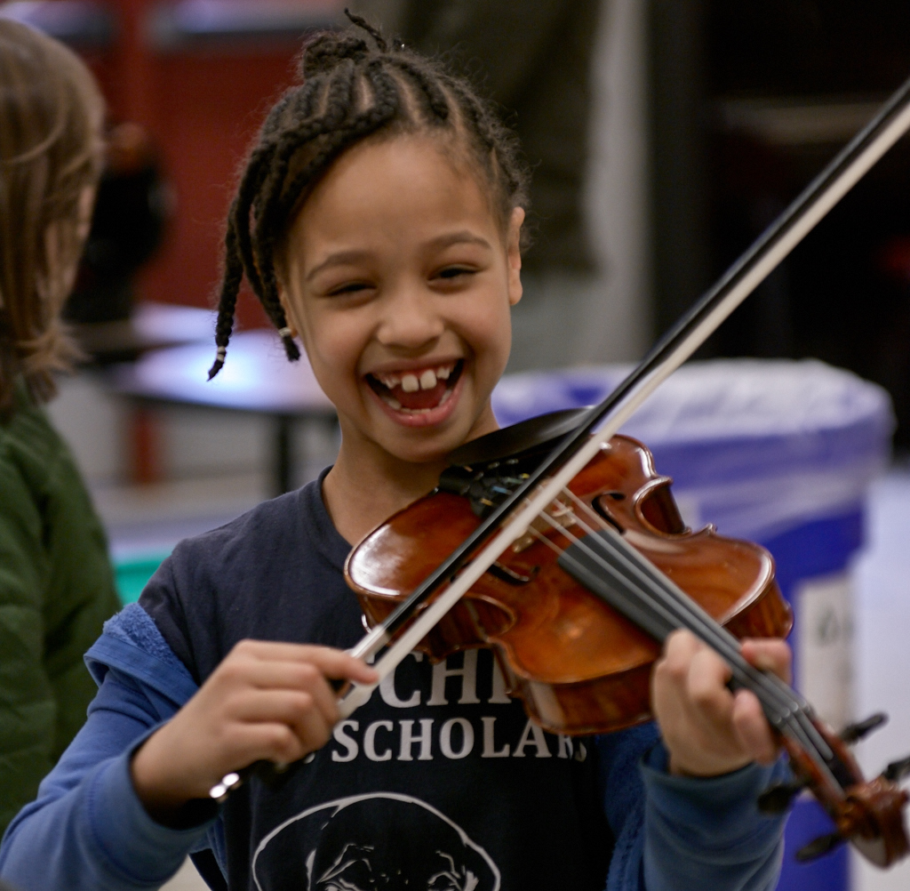 "A 4th grader  at Leschi Elementary School tries out the violin at the ""Instrument Petting Zoo,"" part of the Catalyst Quartet extended residency in Seattle public schools. Photo credit: Phil Lanum."