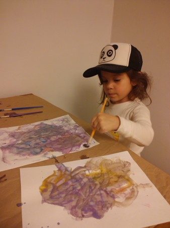 Sofia, age 3,exploring painting with a brush (instead of her fingers).