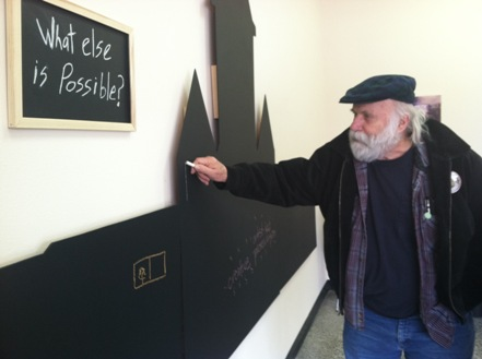 Fergus Falls resident Gene Schmidt writes his ideas on a chalkboard silhouette of the Kirkbride Building (photo by Michele Anderson)