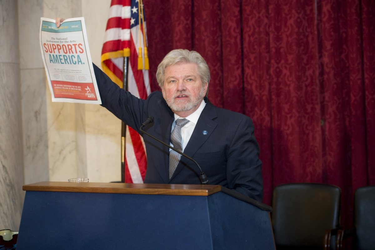 Bob Lynch holds up ads for Arts Advocacy Day that printed in the Capitol Hill newspapers read by members of Congress and staff: Roll Call, Politico, and The Hill. (Photo by Maria Bryk.)