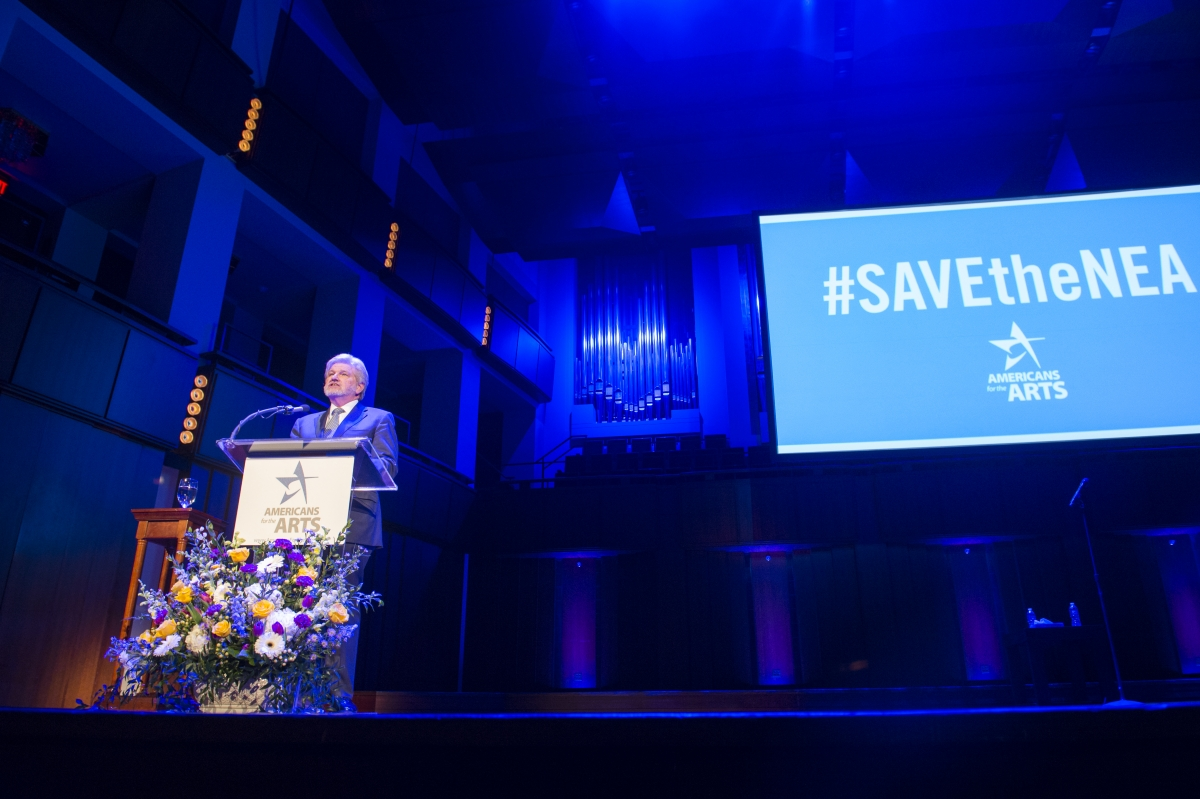 Robert L. Lynch, President & CEO of Americans for the Arts, speaks before the 2017 crowd at the John F. Kennedy Center for the Nancy Hanks Lecture on Arts and Public Policy, including mention of the groundswell #SAVEtheNEA social media campaign. (Photo by Maria Bryk)