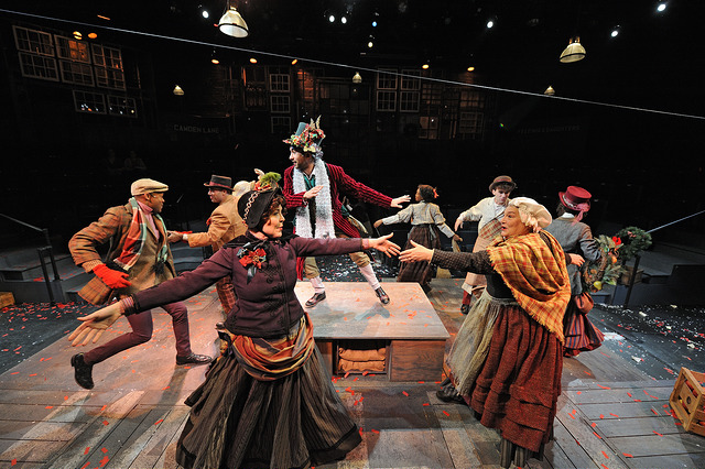 "Orlando Hernandez (center) as Ghost of Christmas Present with the company of ""A Christmas Carol,"" directed by Angela Brazil and Stephen Thorne. Costume design by Toni Spadafora, set design by Michael McGarty, lighting design by Dawn Chiang. Photo by Mark Turek."