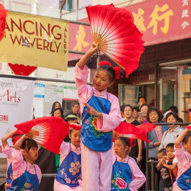 Young children with matching pink costumes, blue floral aprons, and red fans, dance on an outdoor stage.