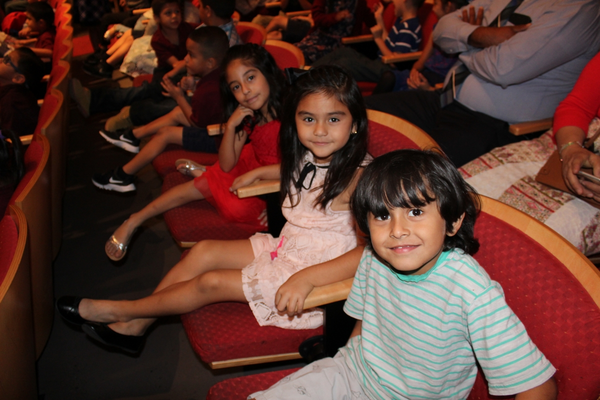 Children sitting in audience at theater field trip performance.