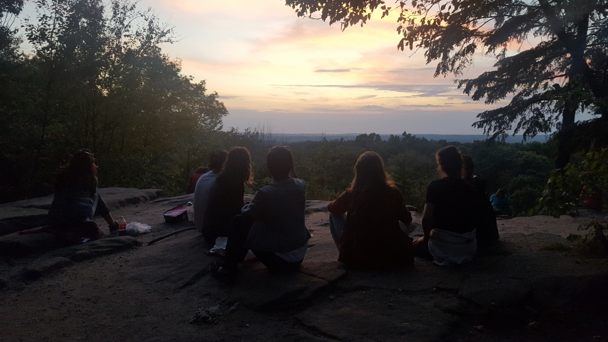 Kimberly Bartosik and BODYTRAFFIC dancers observe sunset in Cuyahoga Valley National Park. Image Description: A group of people with their backs to the camera sit on the ground, silhouetted. They are looking out at a sunset in shades of pink, lavender, and pale gold. The vista is framed on either side by trees, and the horizon is a dark blue-gray line above the treetops in the distance.