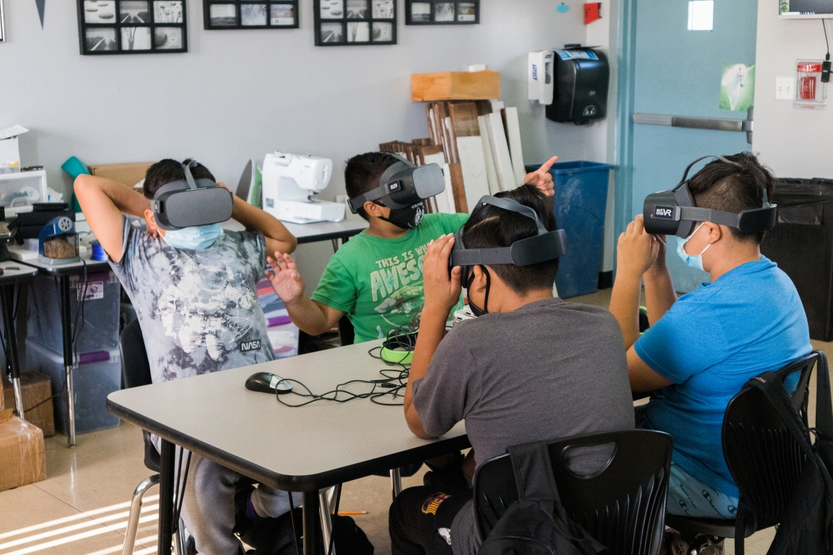 Four young students sit around a classroom table wearing VR headsets, and one student pointing into air.
