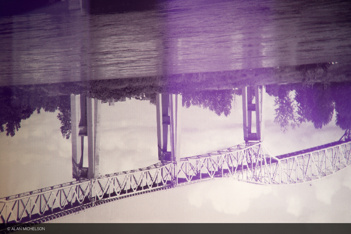 """A detail of """"Third Bank of the River"""" by Alan Michelson focused on an upside down bridge tower and showing the dot-matrix pattern of the artwork."""
