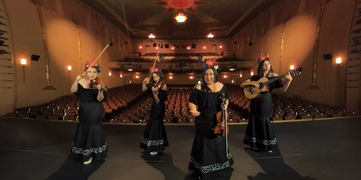 Four-person mariachi band in black dresses on bare stage