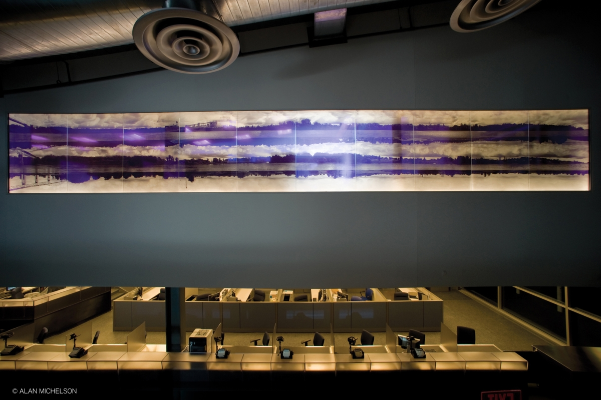 """""""Third Bank of the River"""" by Alan Michelson. Description: A large purple and white artwork depicting riverbanks and bridges hangs on a wall above a room of cubicle desks."""