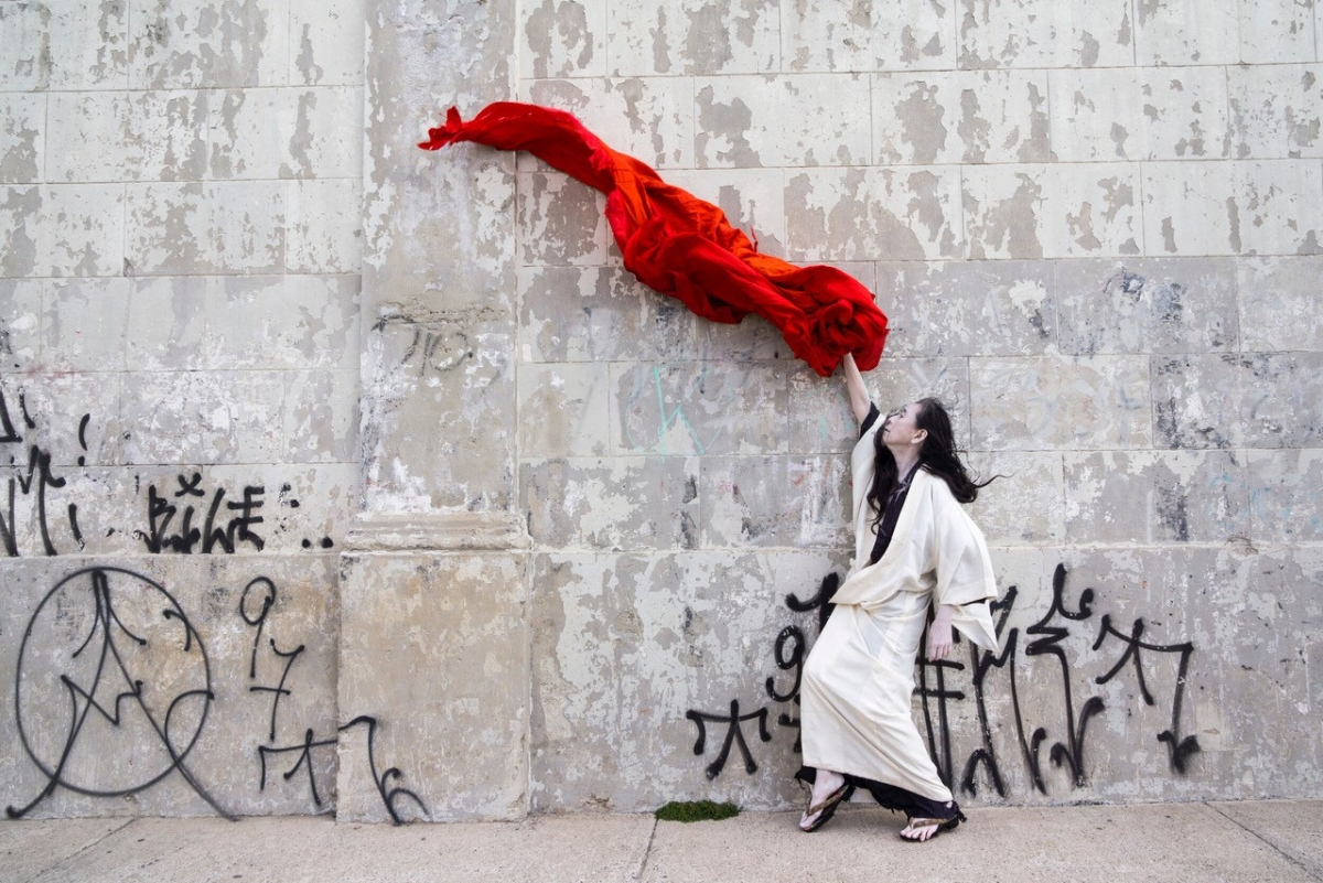 """Dance artist Eiko Otake in an image from """"A Body in Fukushima."""" Photo by William Johnston used with permission. Description: A dancer dressed in white waves a large red cloth in the air in front of a concrete wall adorned with spray painted graffiti written in Japanese characters."""